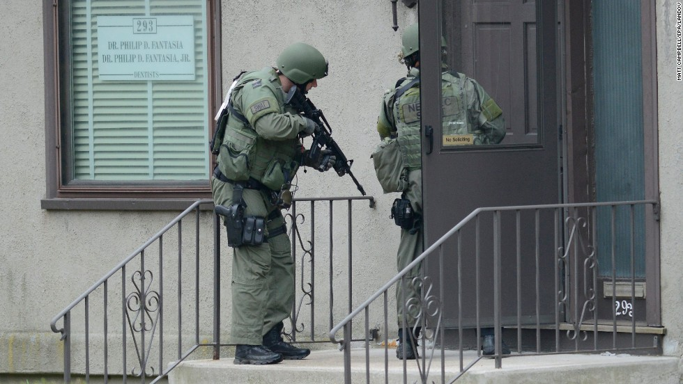 SWAT officers check a door with guns ready on Friday.