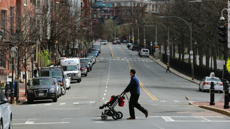 A man crosses a vacant Beacon Street, across from Boston Common.