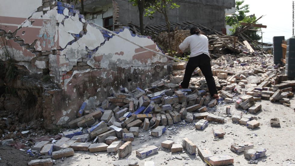 A woman walks on bricks fallen from a collapsed house Saturday in Longmen township.