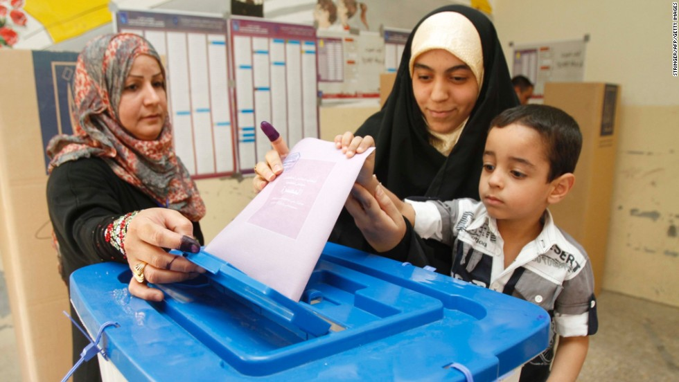 An Iraqi woman casts her vote with the help of her son at a polling station on Saturday.