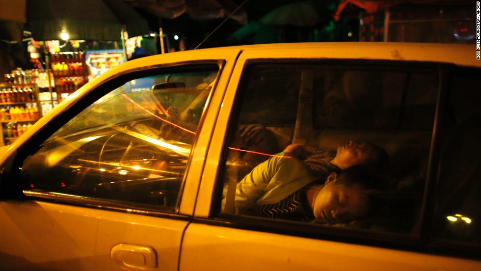 Chinese residents sleep in a car on Sunday to avoid danger from aftershocks.
