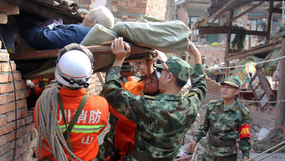 Rescuers carry a paralyzed patient from a collapsed house on Sunday in Qingren township.