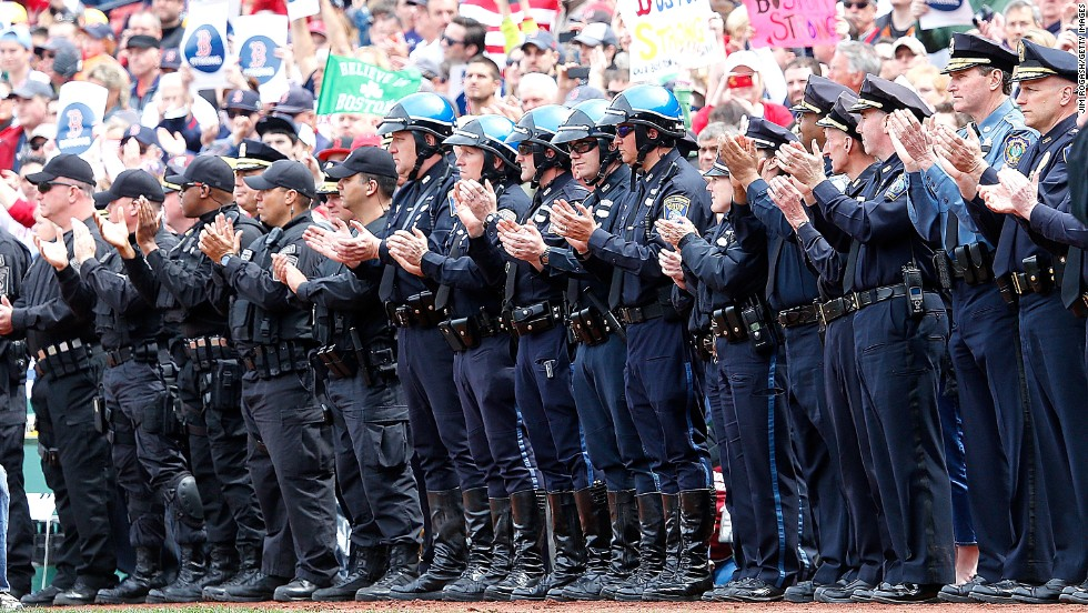 Members of law enforcement react during ceremonies in honor of the Marathon bombing victims before Saturday's game.