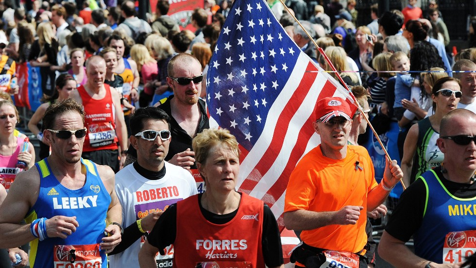 A man carries a U.S. flag as he runs with other marathoners during the London Marathon on April 21.