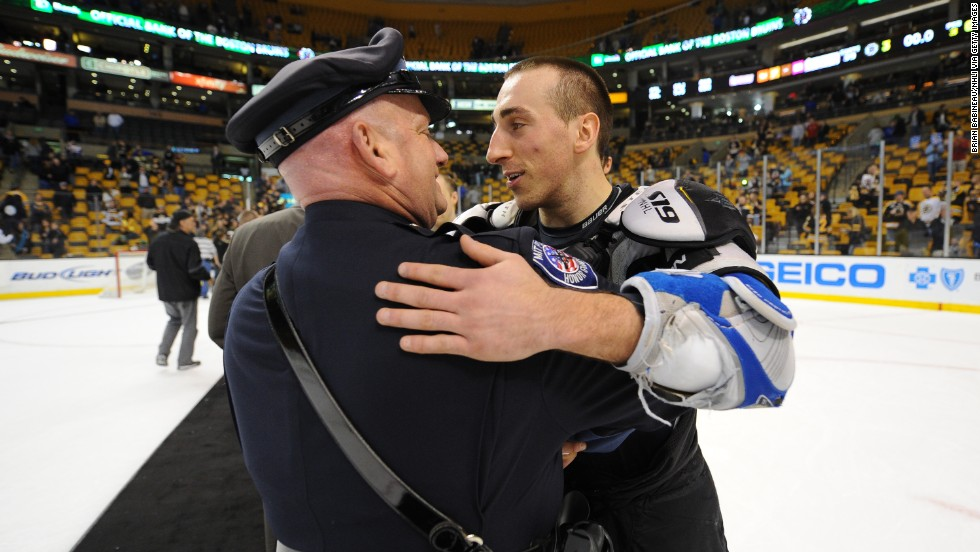 Brad Marchand of the Boston Bruins embraces one of the first responders from the Boston Marathon attack after the game against the Florida Panthers at the TD Garden on Sunday, April 21, in Boston.