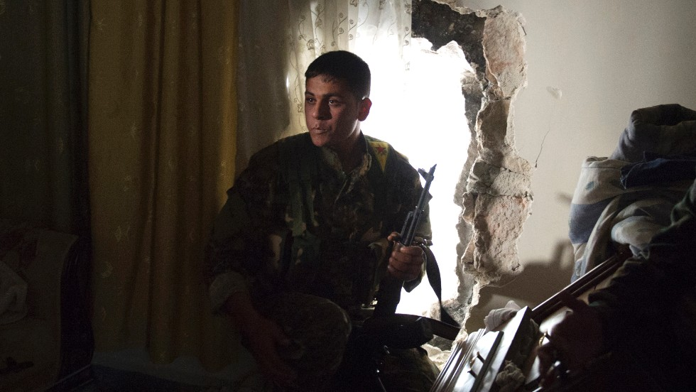 "A Kurdish fighter from the ""Popular Protection Units"" (YPG) takes position inside a building in the majority-Kurdish Sheikh Maqsood area of Aleppo, on Apri. 21."