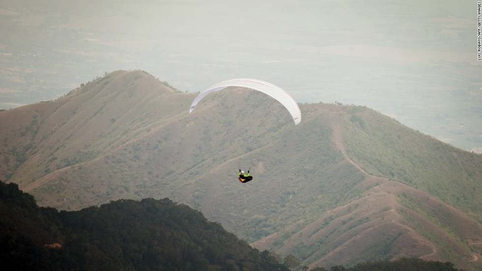 Austrian paraglider pilot Othmar Dickbauer flies above the mountains in Roldanillo, Valle del Cauca department, Colombia, during the Paragliding World Cup Superfinal, January 2013.