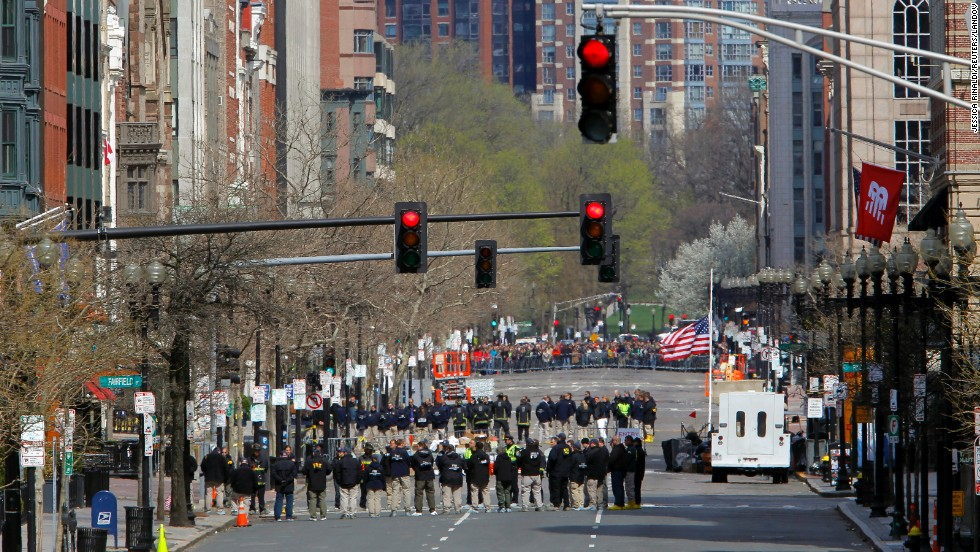 Officials line Boylston Street as they observe a moment of silence near the marathon finish line on April 22, 2013.
