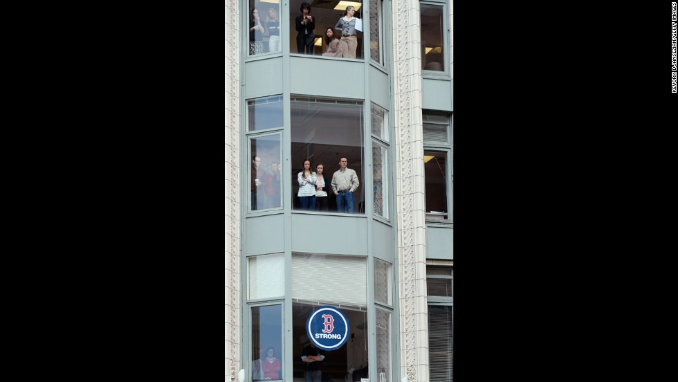 Onlookers at a building near the finish line during a moment of silence on April 22.