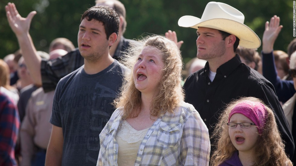 Vanna Wainwright and her daughter Breanna take part in an open air Sunday service on April 21. Members of the First Baptist Church held their service in an open air field after their church was damaged from the explosion.