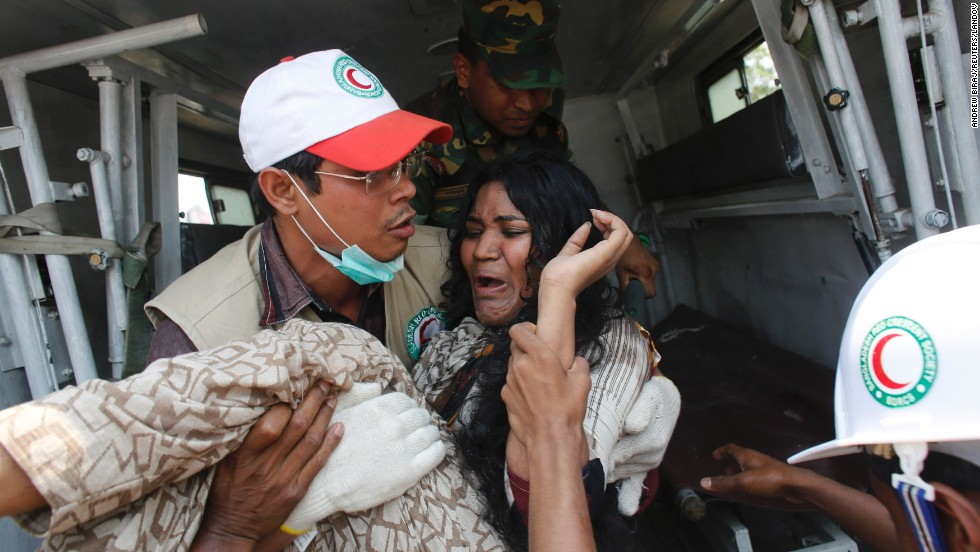 A rescue worker carries a worker to an ambulance on April 24.
