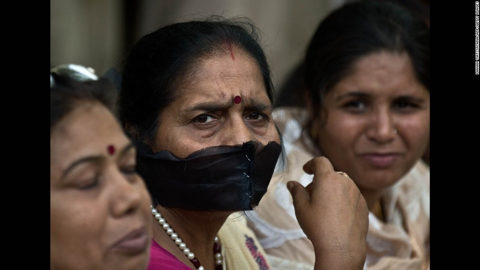 A woman covers her mouth with a black cloth during Tuesday's protest in New Delhi.