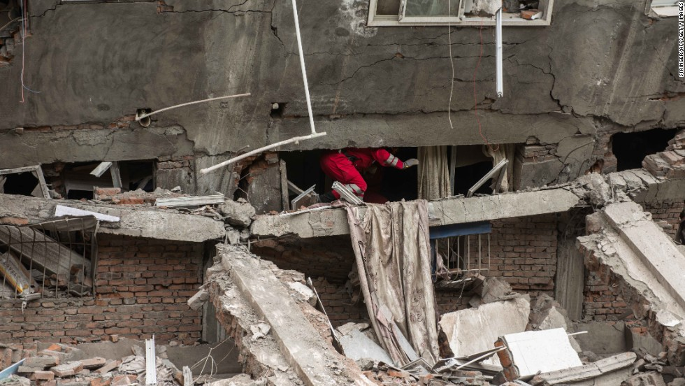 Rescuers check a collapsed building in Lingguan township in Ya'an.
