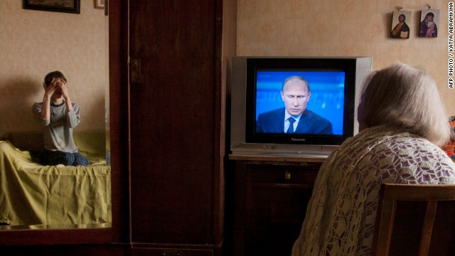 An elderly woman watches President Vladimir Putin's televised question and answer session in Moscow, on April 25, 2013.