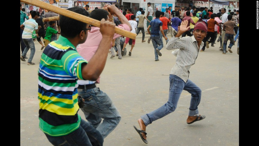 Plainclothes Bangladeshi police brandish sticks as they attempt to break up protests.
