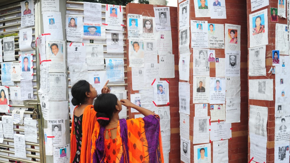 Two Bangladeshi women look at a board with notices posted of missing and dead workers on April 27.