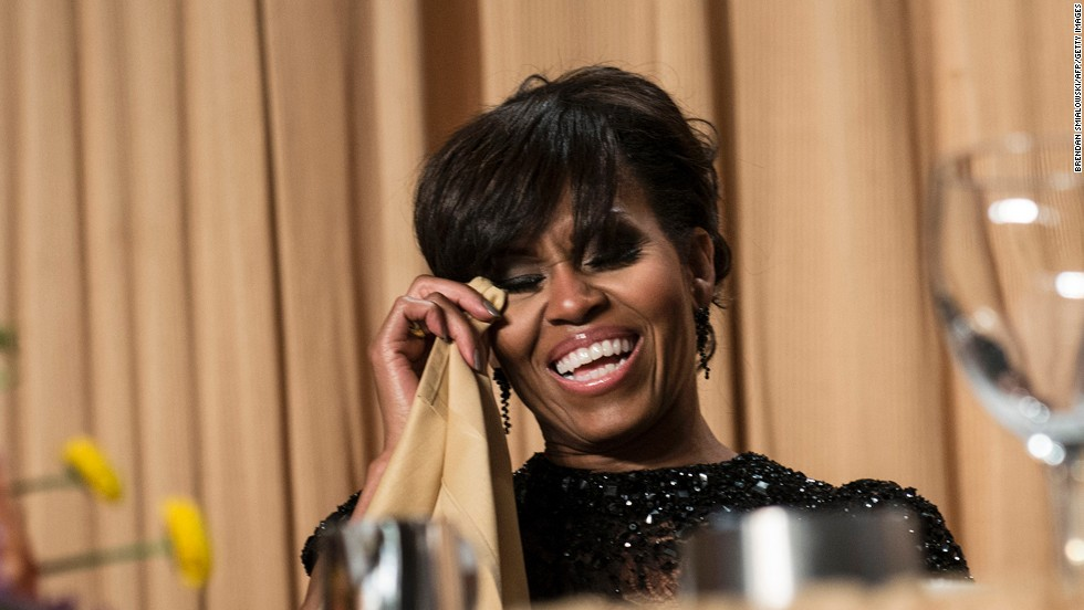 Michelle Obama dabs her eyes while laughing during the dinner