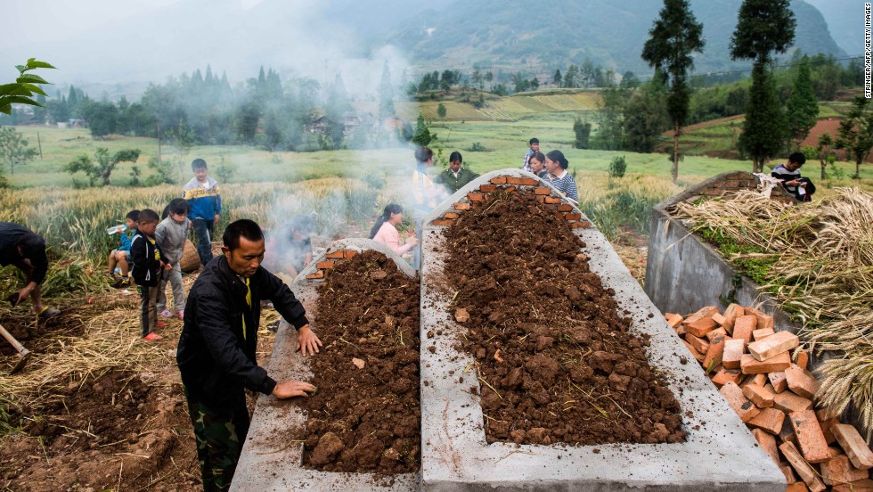 People pay their respects at a newly built grave in Ya'an, China, on Saturday, April 27, one week after a 6.6-magnitude earthquake. More than 190 people died and thousands were injured after the quake struck China's southwest Sichuan province on April 20, state media reported.