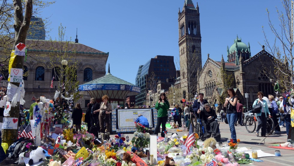"People pause at the memorial site in Copley Square on April 30  in Boston. The city continues to return to normalcy with Boylston Street fully reopened and businesses back up and running after two weeks of closures. <a href=""http://www.cnn.com/SPECIALS/us/boston-bombings-galleries/index.html"">See all photography related to the Boston bombings.</a>"