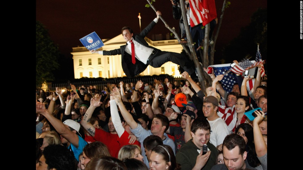 Revelers gather at the fence on the north side of the White House.