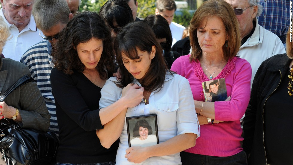 Danielle LeMack, left, Carie LeMack and Christie Coombs, who lost relatives on 9/11, pause during a ceremony to honor the victims on May 2, 2011, at the Garden of Remembrance in Boston.