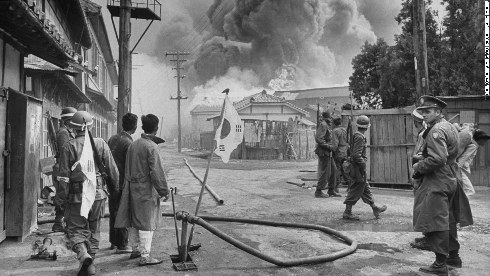 """Korean and U.S. soldiers watch large fires consume a village during an uprising in 1948. Two years before the Korean Peninsula erupted in a civil war, communist rebels -- many of whom had been in the American-trained Korean army -- revolted against President Syngman Rhee's regime. Photographer Carl Mydans was on the ground when the rebellion began. Most of his pictures have never been published before. <a href=""""http://life.time.com/history/korea-photos-from-the-october-1948-rebellion/"""" target=""""_blank"""">View more at LIFE.com.</a>"""