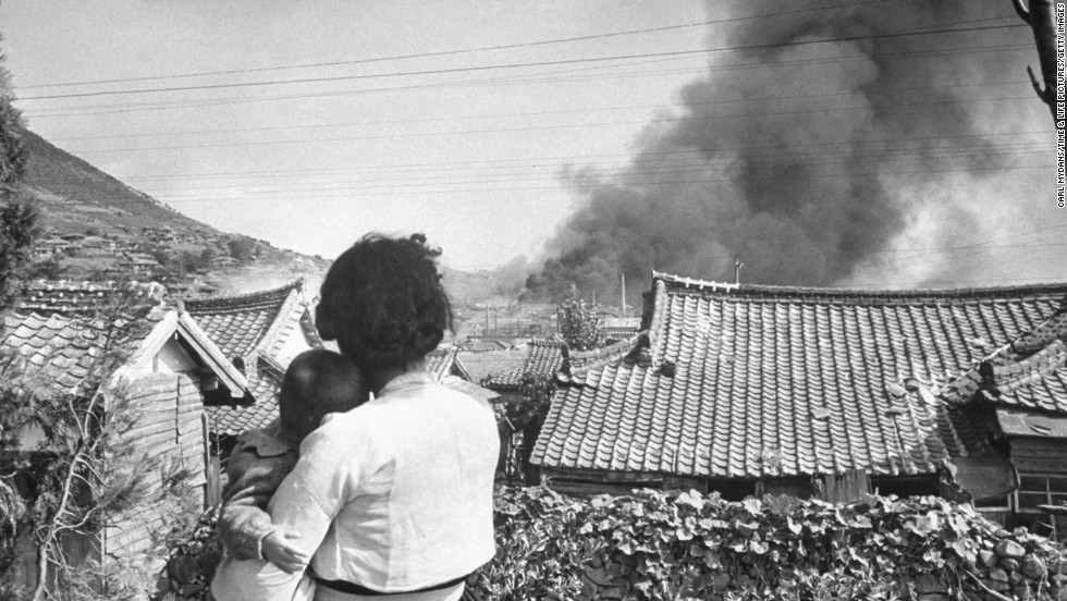 A woman and child watch as a village burns.