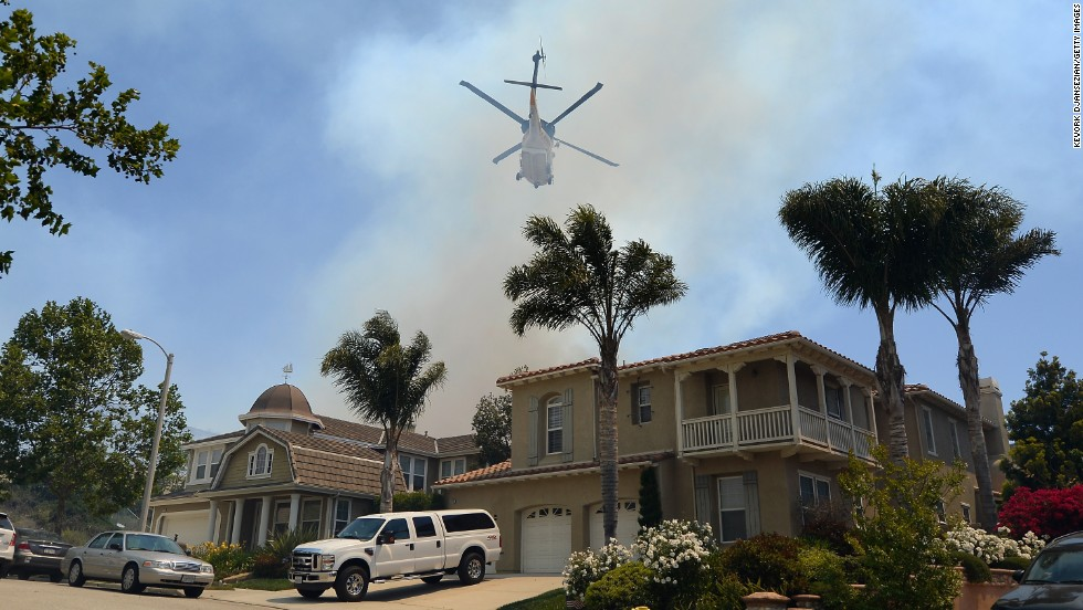 A firefighting helicopter comes in to make a water drop behind homes threatened by the fire on Thursday.  Ninety-six fire engines, six helicopters and five bulldozers have been deployed in battling two California wildfires in the Los Angeles area, according to fire authorities.
