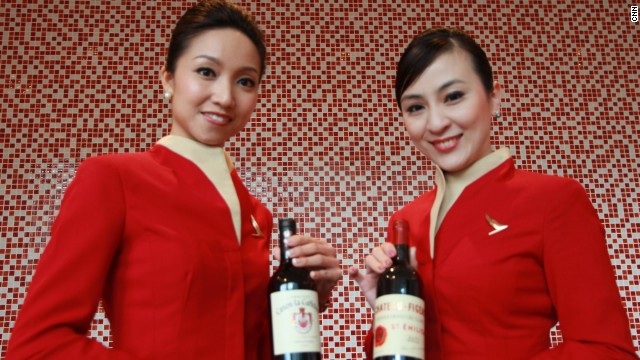 Cabin cru: Cathay Pacific stewardesses proffer the airline's latest reds