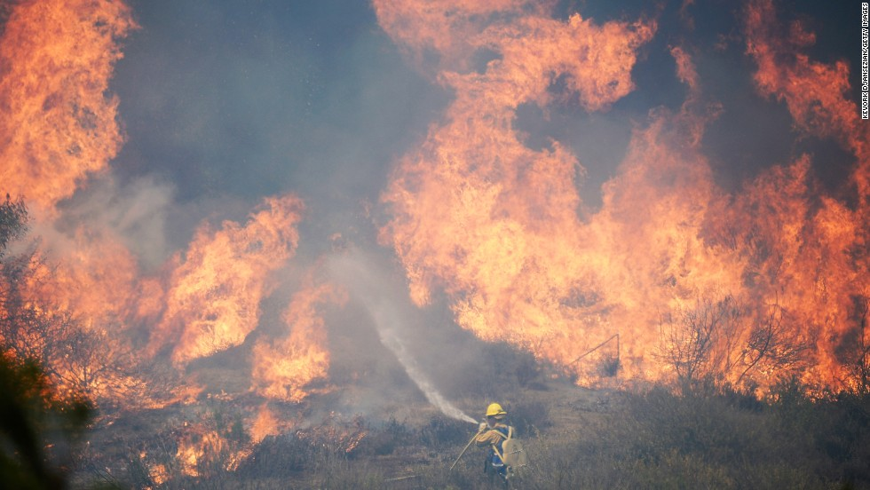 A firefighter works against a wall of flames from an out-of-control wildfire on Thursday, May 2, in Camarillo, California.