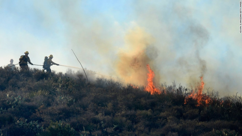 Firefighters put out hot spots on a hillside behind homes in Newbury Park on May 2.