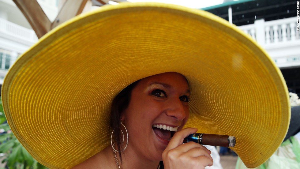 A fan's wide-brimmed hat protects her cigar from the rain.