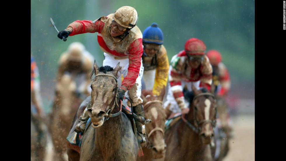 Rosario rejoices atop a mud-splattered Orb after winning the race.