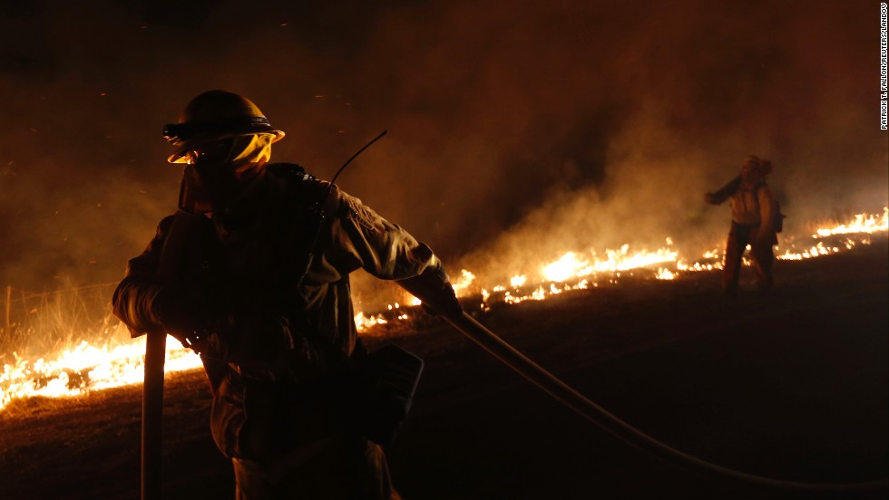 A firefighter pulls a hose line near a backfire while fighting the Springs Fire on May 4.