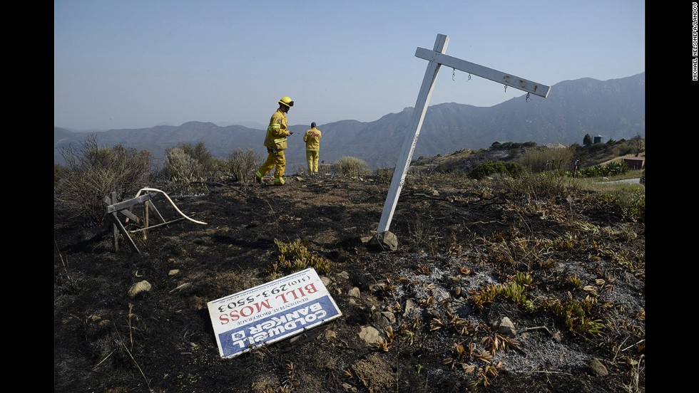 Firefighters monitor the fire-scorched hills near Point Mugu State Park on May 4.