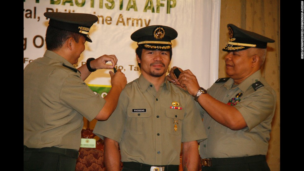 Pacquiao is conferred the rank of lieutenant colonel by Maj. Gen. Emmanuel Bautista, left, and Brig. Gen. Alex Albano, right, in Manila, on December 5, 2011.