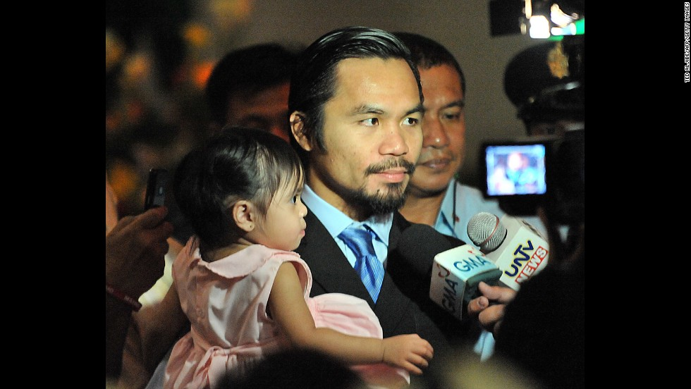 Pacquiao holds his daughter Queen Elizabeth as he talks to members of the media during his victory party for winning a seat in parliament -- held jointly with her birthday celebration -- at a convention center on the southern island of Mindanao on May 15, 2010.