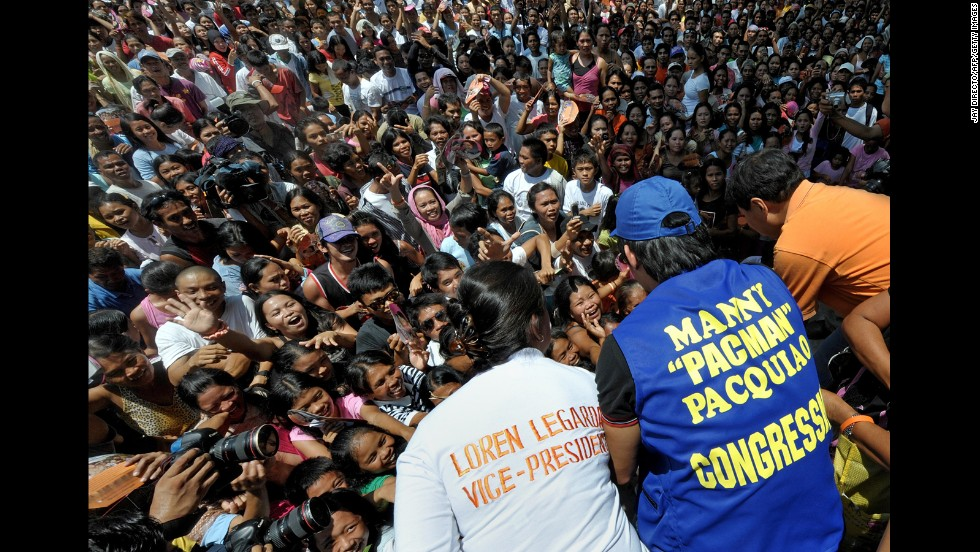 Pacquiao, center, greets supporters with presidential candidate Manny Villar, right, and vice-presidential candidate Loren Legarda, left, as he starts his campaign for Congress in March 2010.