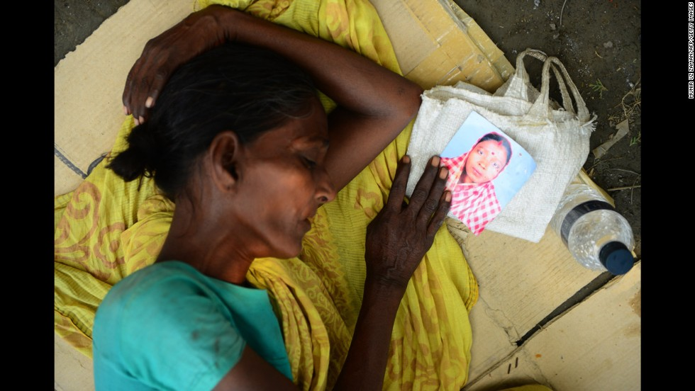 A woman holds a portrait of her missing relative as she sleeps on Saturday, May 4.