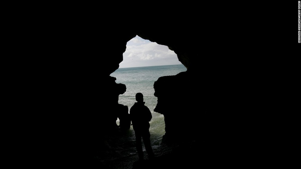 A tourist looks out from the Hercules Grotto near Tangier on November 25, 2007.