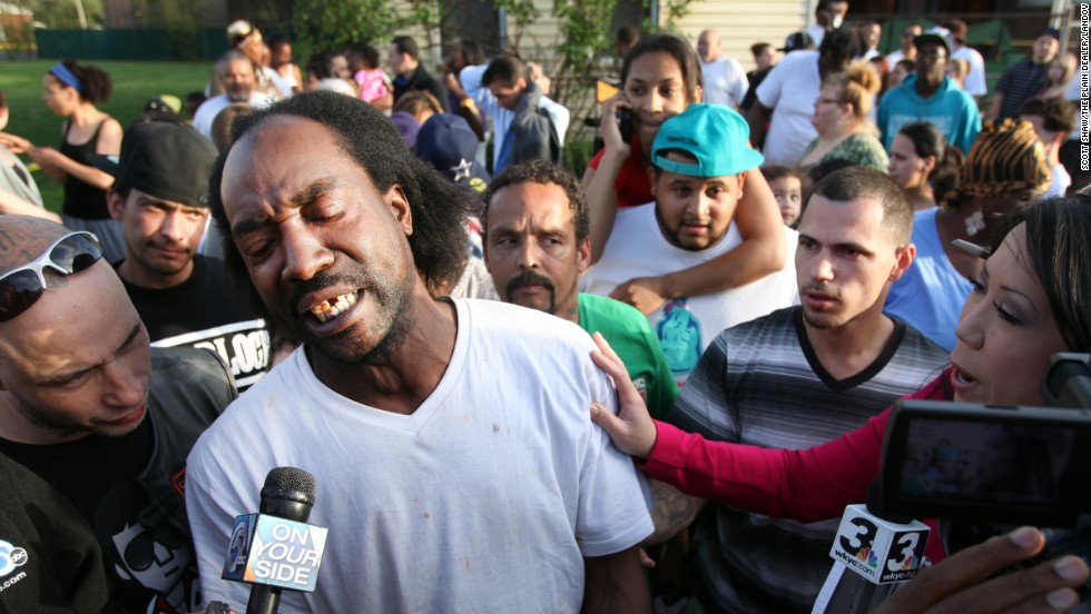 Neighbor Charles Ramsey talks to media as people congratulate him on helping the kidnapped women escape on May 6, 2013. He helped knock down the door after he heard screaming inside.