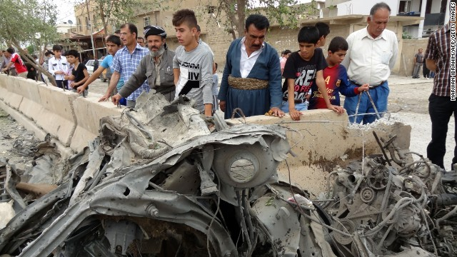 Iraqi Kurds look at the remains of a car bomb on May 8, 2013, in the northern city of Kirkuk.