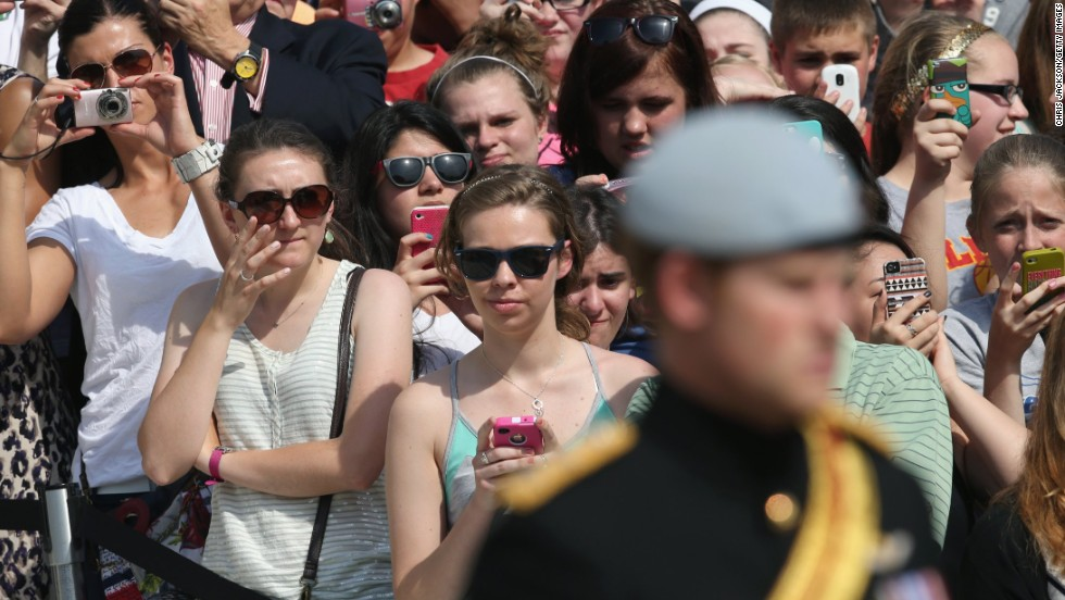 Onlookers take pictures as Prince Harry visits the Tomb of the Unknowns at Arlington National Cemetery.