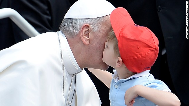 Pope Francis is kissed by a boy on Sunday in St.Peter's Square at the end of a canonization service.
