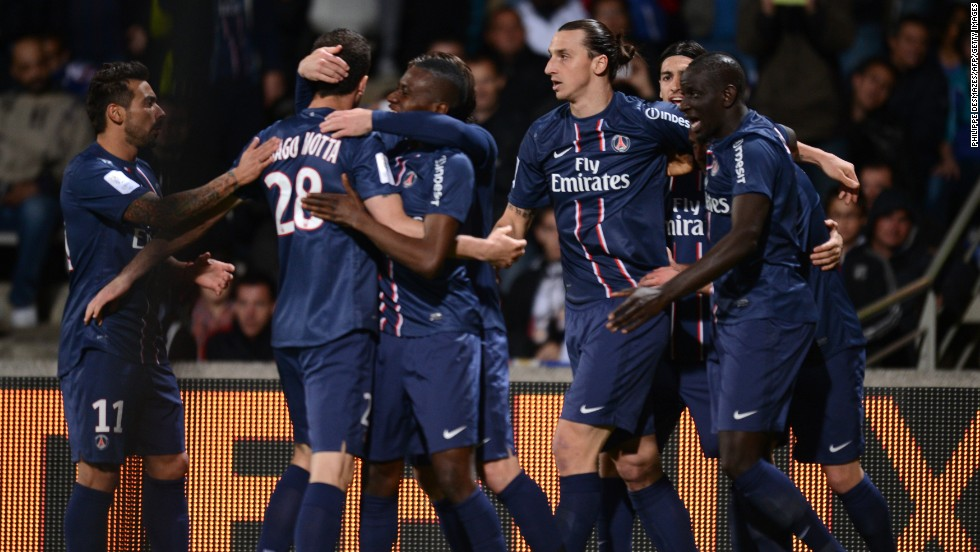 Jeremy Menez is mobbed by his teammates after scoring the winning goal at Lyon that secured Paris Saint-Germain's first French title since 1994.