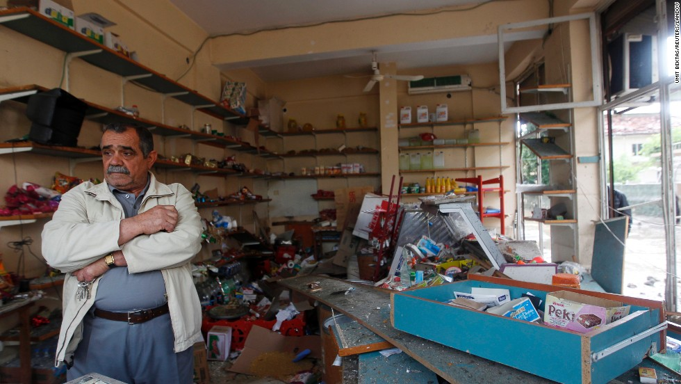 "A shop owner stands in his damaged shop on Monday, May 13, at the site of a deadly twin bomb blast in the town of Reyhanli in Hatay province, near the Turkish-Syrian border. <a href=""http://www.cnn.com/2013/05/13/world/meast/turkey-syria-violence/index.html"">Turkey has blamed Marxists with Syrian connections</a> for the May 11 attacks."