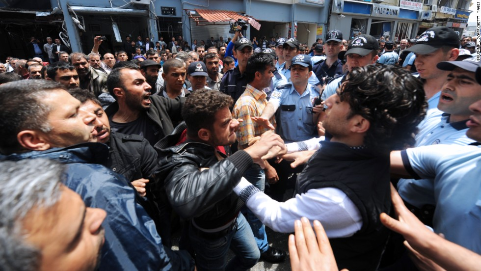 People try to stop relatives of a victim of the bombings as they argue with police officers on May 13 in Reyhanli. The bombing left at least 47 dead and around 100 injured after two explosive-laden cars exploded in the street.