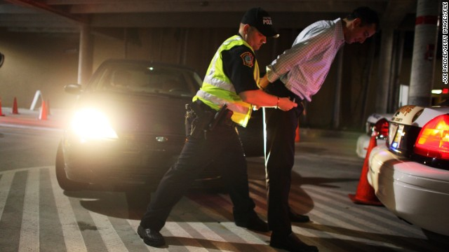 A police officer arrests a driver who failed a field sobriety test at a DUI traffic checkpoint in Miami, Florida.