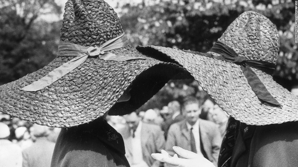 Hat to hat chat....two women in straw hats chat during a visit to the 1964 Chelsea Flower Show