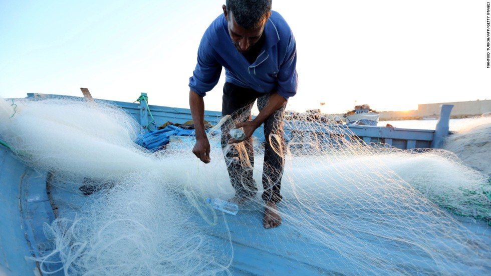 A man inspects his fishing net in the port of Tripoli on November 3.